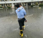 滂沱大雨中,社区民警抱送幼儿园孩子趟水上学...